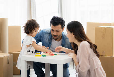 Parents and daughters play with wooden blocks sitting on the floor in the living room at home. The family just moved to a new house. Happy moment Multi-ethnic dad mom and child.