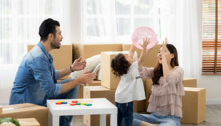 Parents and daughters play with pink balloon sitting on the floor in the living room at home. The family just moved to a new house. Happy moment Multi-ethnic dad mom and child. Standard-Bild