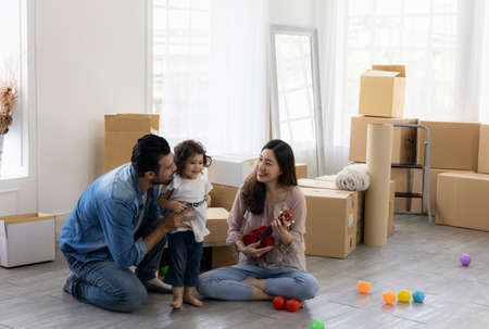 Parents and daughters play with ukulele sitting on the floor in the living room at home. The family just moved to a new house. Happy moment Multi-ethnic dad mom and child.