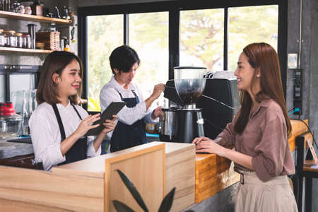 A customer orders a hot latte to the barista. Asian Staff coffee shop cafe making hot coffee and serve to customer. Small business sme concept. Standard-Bild