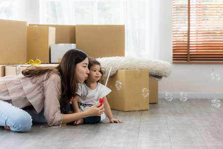 Happy time family blow soap bubbles relax in living room. Everyone having fun in the house. Standard-Bild