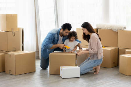 The family just bought new furniture and helped organize the house. Mon dad and daughter just moving new home. They unpacking parcel box and arranging on the floor in the living room.