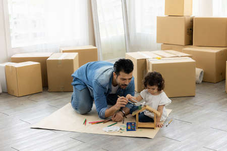 Father and daughter painting coloring with watercolor on the wooden house mock up. Sitting on the floor in living room. Happy family moment in the house. Art Activity in kindergarten.