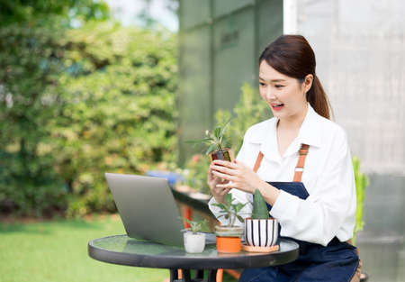 Beautiful Asian young woman greenhouse worker selling Small tree on social media live stream with laptop. Landscaping small plants and decorating the garden in the house. Gardener working house plant. Standard-Bild