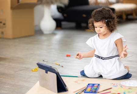 Cute daughter painting coloring with watercolor on the large paper Learning by tablet. Sitting on the floor in living room. Happy kid moment in the house. Art Activity in kindergarten. Standard-Bild