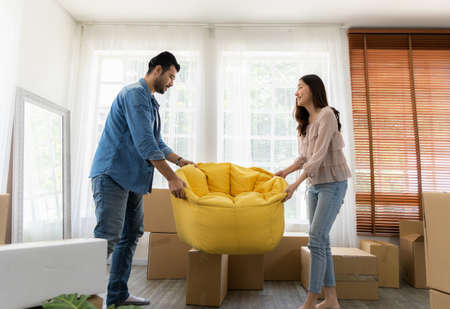 The family just bought new furniture and helped organize the house. Husband and wife just moving new home. They unpacking parcel box and arranging on the floor in the living room.