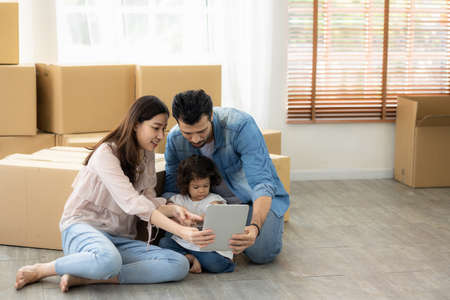 Family relaxing at home. Father mother and daughter using tablet watching movies, play game and video conference. Digital Lifestyle Concept. Standard-Bild