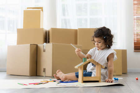 Cute daughter painting coloring with watercolor on the wooden house mock up. Sitting on the floor in living room. Happy kid moment in the house. Art Activity in kindergarten. Standard-Bild