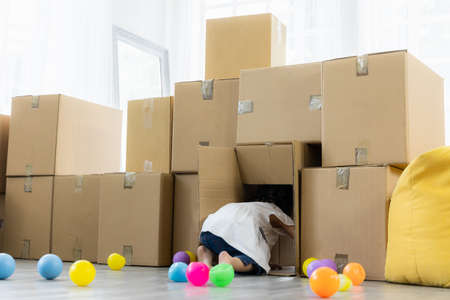 Daughter playing with parcel cardboard. Relaxing in living room in the house. Happy family enjoying relocation