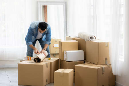 Young man just moving new house. He unpacking parcel box and arranging on the floor in the living room. Standard-Bild