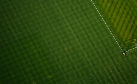 Aerial perspective of mowing pattern in football training field.
