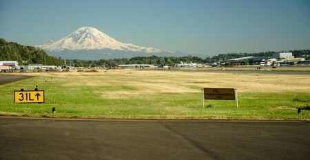 airplane landing: Mt Rainier towers above approach end of Boeing Field as small airplane approaches