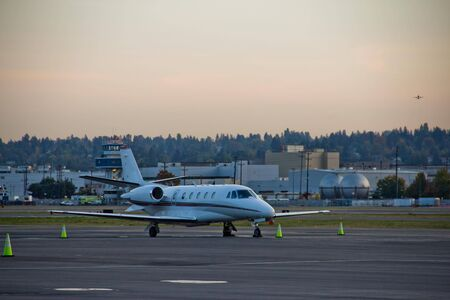 Midsize corporate jet parked at sunset with airplane taking off in background