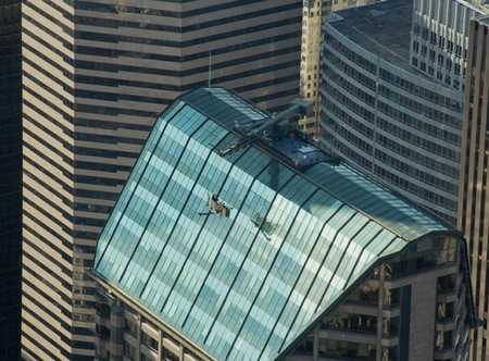 Three window cleaners getting roped back up to the top of a building in downtown Seattle