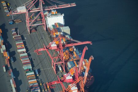 unloading: Aerial perspective of a freight ship unloading containers in Seattle Editorial