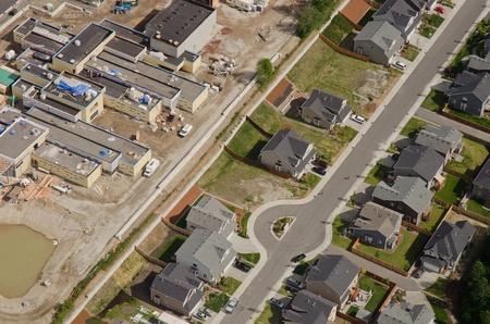 静かな郊外の家の後ろに新しい小売りの開発の航空写真