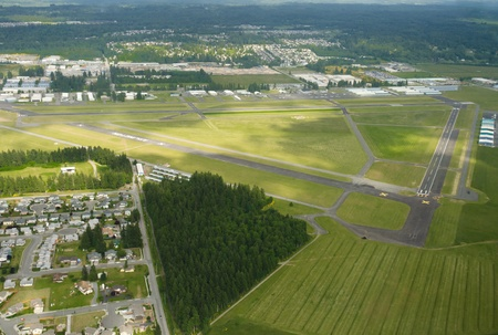 Lush green airport on partially cloudy day photo
