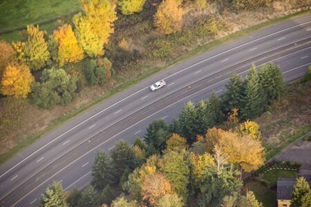 Aerial view of small commuter car driving up hillside road