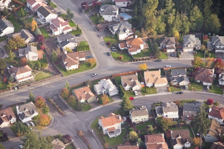 subdivision: Aerial view of single car driving on a neighborhood road
