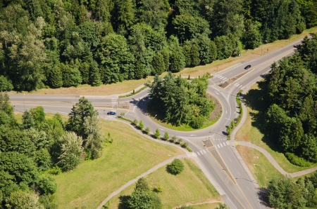 Two cars approach roundabout from opposite sides