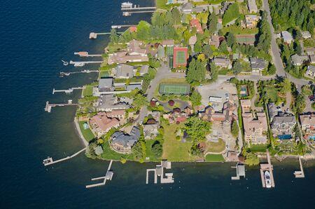 Aerial perspective of rich homes by lake 版權商用圖片