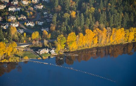 Aerial view of yellow trees reflecting off of calm lake water next to a wealthy residence