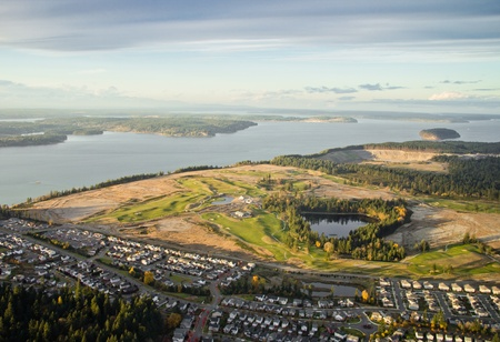 Aerial view of a golf course on a peninsula near Puget Sound at sunset