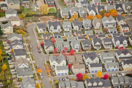 Aerial view of suburban homes with changing leaves on the trees