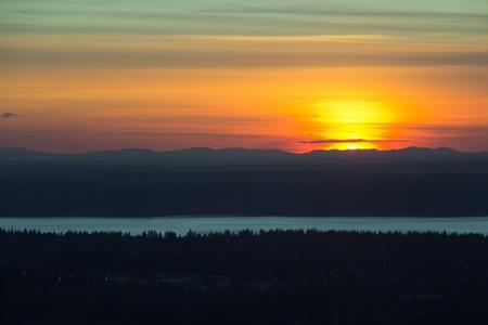 森林、湖、山々 に沈む夕日の空撮 写真素材