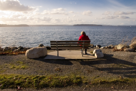 Single, elderly woman sitting on park bench