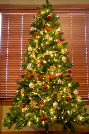Brightly lit and colorfully decorated Christmas tree in front of window