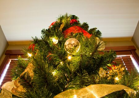 Brightly lit and colorfully decorated Christmas Tree in front of a window Stock Photo