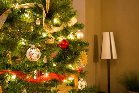 Brightly lit and colorfully decorated Christmas Tree next to a lamp Standard-Bild