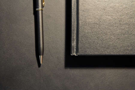 Gold and Black Pen and Matte Booklet on Black Table Stock Photo