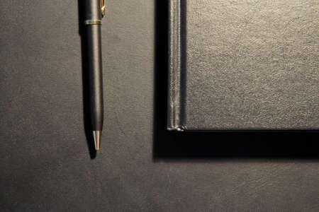 Gold and Black Pen and Matte Booklet on Black Table Standard-Bild