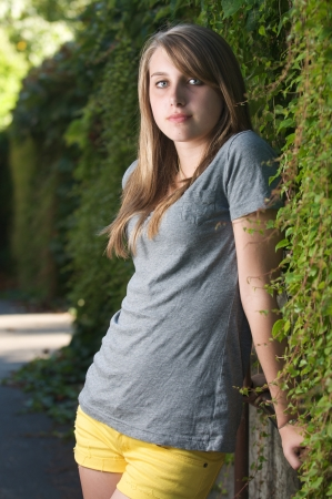 Vertical teenage girl stands near vines in the shade