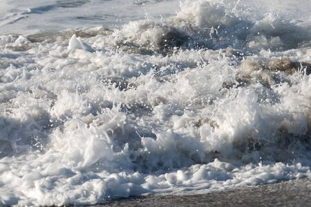 foamy: Close up of foamy ocean waves on a sunny day