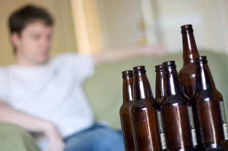 facing right: Man facing right at a group of empty beer bottles, angled Stock Photo
