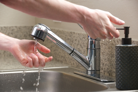 sink drain: Hands reach for soap at the kitchen sink