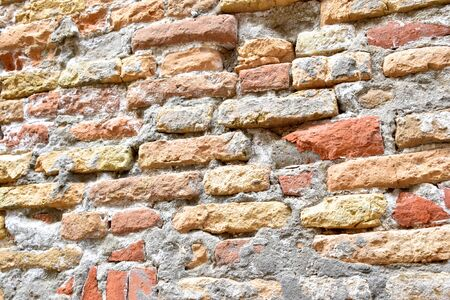 Brick wall is worn and textured by weather Stock Photo