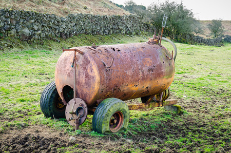 A rusty, corroded slurry tanker with punctured tyres sits abandoned in a muddy field in the Irish countryside. Standard-Bild