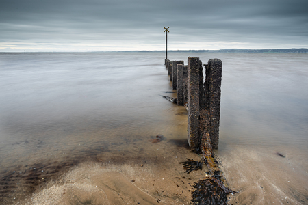 A collapsing sea groyne on Carrickfergus beach, County Antrim, Northern Ireland. Stock Photo