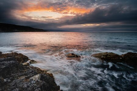 Portmuck, Islandmagee, County Antrim, Northern Ireland: A sunset and cloud formation create the appearance of a fiery hole in the sky.