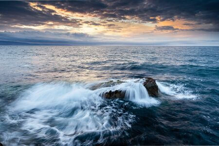Portmuck, Islandmagee, County Antrim, Northern Ireland:  under a dramatic sunset sky, waves break over rocks close to the shore.