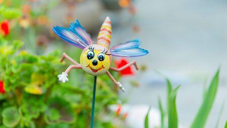 Ein neuartiges Libellen-Gartenornament, das auf einem Stiel in einem Blumenbeet in einem heimischen Garten positioniert ist