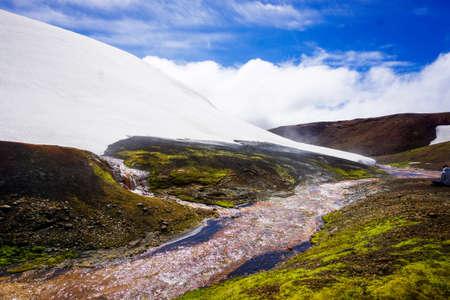 Misty river running through a mountain snowbank