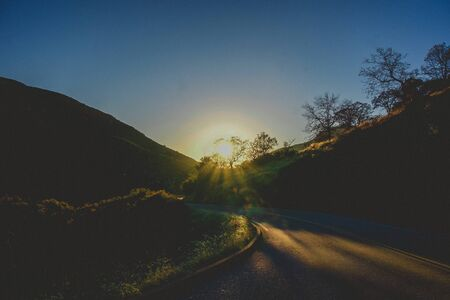 moody sunlight on the winding road in the mountains Stock Photo