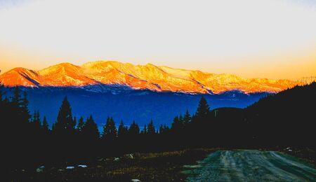 orange and blue sunrise with evergreens