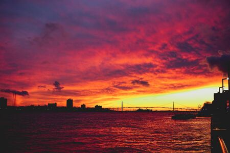 orange and pink sunset on the Detroit river looking at the Ambassador Bridge