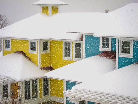 snow falling on colorful houses Stock Photo